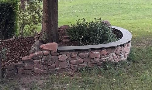 Sandsteinmauer und Kräuterbeet rund um die Linde
